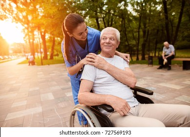 The nurse carefully laid her hand on the old man's shoulder, who was sitting in a wheelchair. The nurse is smiling and looking at the old man, and the old man is at her
