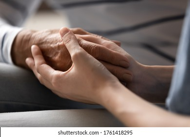 Nurse caregiver or grown up daughter granddaughter holding hand of elderly mother grandma or patient express care close up view, relative overcome together through life troubles disease griefs concept