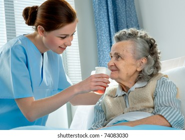 Nurse cares for elderly woman lying in bed