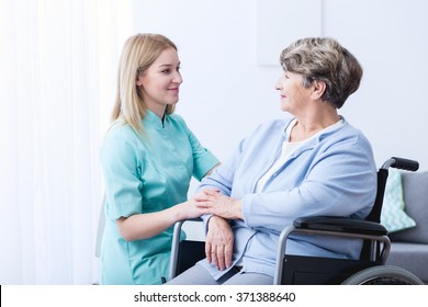 Nurse caring about elder woman at home