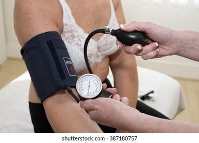 Nurse checking elderly woman's blood pressure using a blood pressure monitor