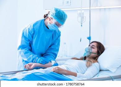 Krankenschwester, die während der Covid-19-Pandemie eine intravenöse Tropfinfusion auf einen kranken Patienten mit einer positiven Drucksauerstoffmaske im Krankenhaus überprüft