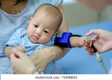 Nurse überprüft Drucktest Baby ein asiatischer kleiner Junge in den Armen der Mutter im Krankenhaus