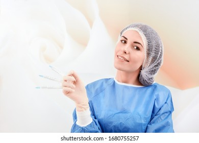 A nurse at the clinic, dressed in protective clothing, holding three syringes in her hand