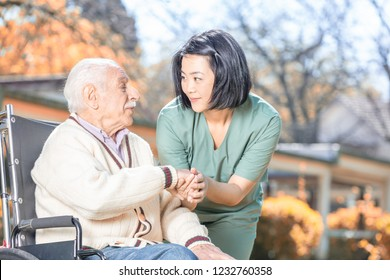 The nurse is consoling an elderly man in a wheelchair.