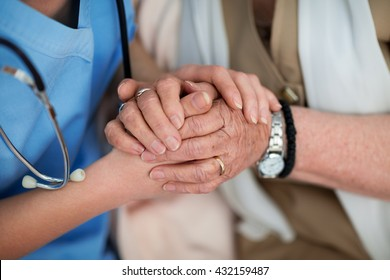 Nurse consoling and holding hands of an old woman