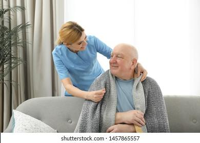 Nurse covering elderly man with blanket indoors. Assisting senior people