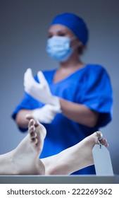 Nurse and dead body in morgue, vertical
