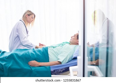 Nurse discussing take care of man patients closely on patient's bed in hospital