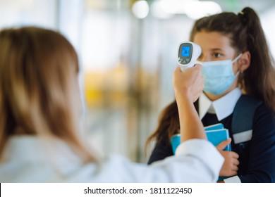 Nurse or doctor checks children body temperature using infrared forehead thermometer (gun) for virus symptom - epidemic outbreak concept. Back to school in quarantine. Covid-19.