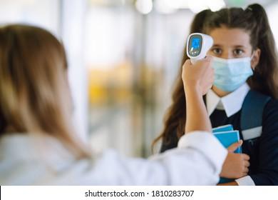Nurse or doctor checks Schoolgirl body temperature using infrared forehead thermometer (gun) for virus symptom - epidemic outbreak concept. Back to school in quarantine. Covid-19.