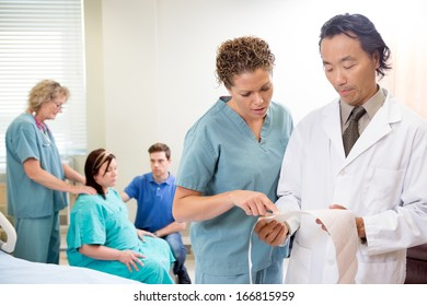 Nurse and doctor discussing fetal monitor report in maternity ward