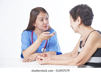 Nurse or doctor giving medical advice to an elderly patient.
