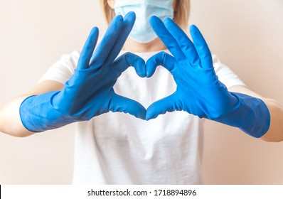 Nurse doctor hands in blue medical gloves in the shape of heart against the background of her body. Close up. Blurred background. Thanks to health workers concept. Gratitude to the medical staff.