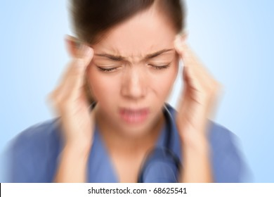 Nurse / doctor with migraine headache overworked and stressed. Health care professional.