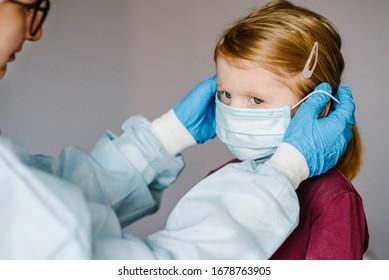 Krankenschwester, Arzt in einem Schutzanzug, mit medizinischer Maske auf dem Gesicht für Kinder. Präventivmaßnahmen gegen Covid-19-Infektionen. Konzept des Schutzes gegen Grippe, Corona-Virus-Epidemie.