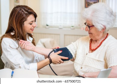 Nurse doing blood pressure monitoring for senior woman at home.