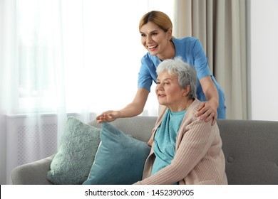 Nurse with elderly woman indoors, space for text. Assisting senior people