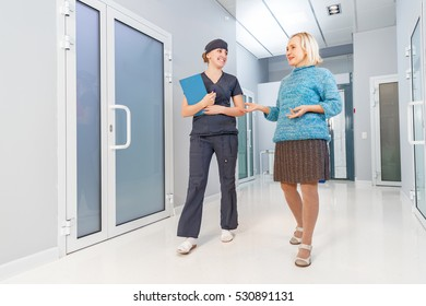 Nurse with an elderly woman patient walk along hall