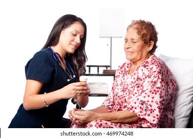 Nurse explaining prescription medication to senior patient, home medical health concept.