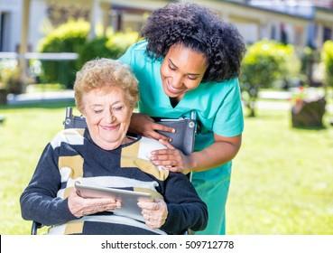 Nurse explaining tablet use to elder woman on wheelchair.