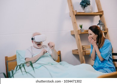 Nurse feeling excited about old man using vr glasses in bed