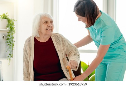 Nurse giving cane to old woman living in home for elderly