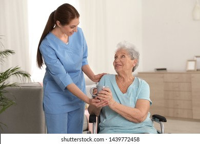 Nurse giving cup of tea to woman in wheelchair indoors. Assisting senior people