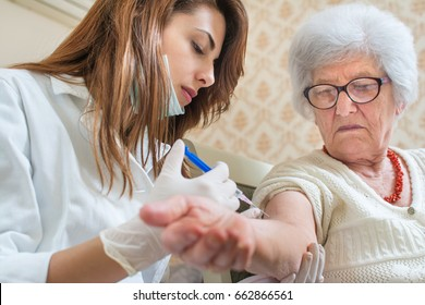 Nurse giving injection to senior woman. Home care.