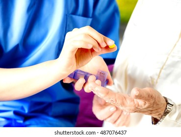 Nurse giving pill to elder people, hands detail.