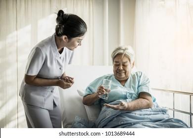 Nurse giving senior woman medical pills.