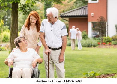 Nurse and grandmother in a wheelchair next to elderly man with walking stick