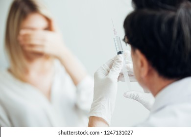 Nurse hand with syringe needle and woman fear of injections phobia concept against