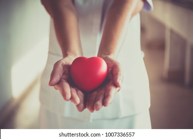 Nurse hands holding red heart in hospital.healthy and medichine concept and selective focus