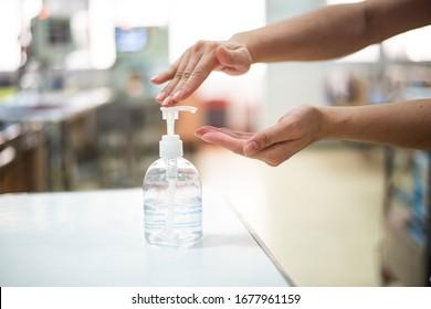 Nurse hands using wash hand sanitizer gel pump dispenser before  nursing care a patient in hospital ward,Disinfection concept.