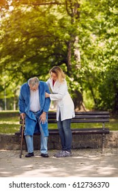 Nurse helping elderly disabled man outdoor