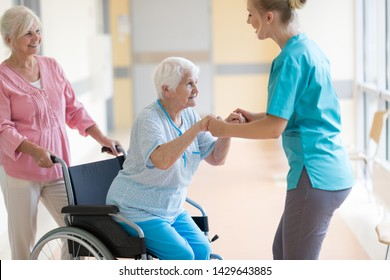 Nurse helping elderly woman in wheelchair