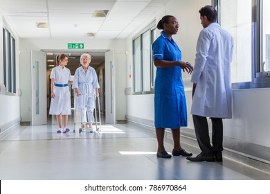 Nurse helping a female elderly old woman patient using walking frame in a hospital corridor with a doctor