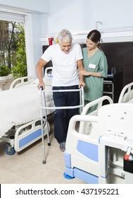 Nurse Helping Male Patient In Using Walker At Rehabilitation Cen