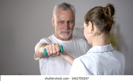 Nurse helping old man to lift dumbbell, cardiac rehabilitation, injury recovery