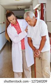 Nurse helping senior man with cane in a nursing home