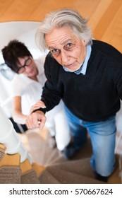 Nurse Helping Senior Man Climbing Stairs