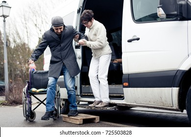 Nurse Helping Senior Man Exit A Van
