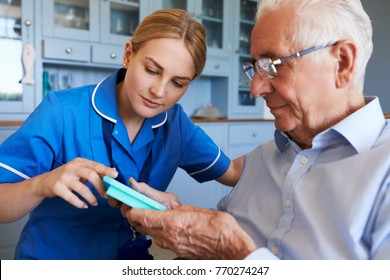 Nurse Helping Senior Man To Organize Medication On Home Visit