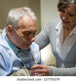 Nurse helping senior sick man with drinking glass of water
