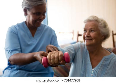 Nurse helping senior woman in lifting dumbell at retirement home