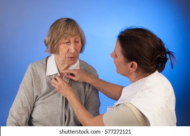 nurse helps a senior woman with dressing in a homecare situation