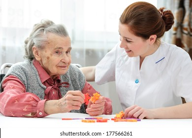 Nurse helps the senior woman jigsaw puzzle to solve in a nursing home