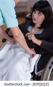 Nurse helps young woman on wheelchair, vertical