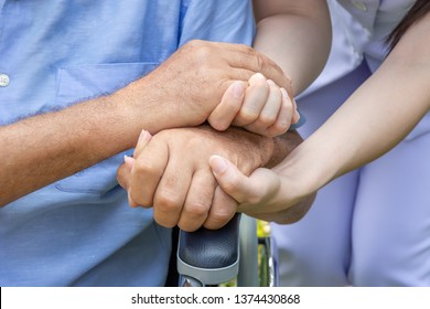 Nurse holding elderly man hand on wheelchair in garden close up
